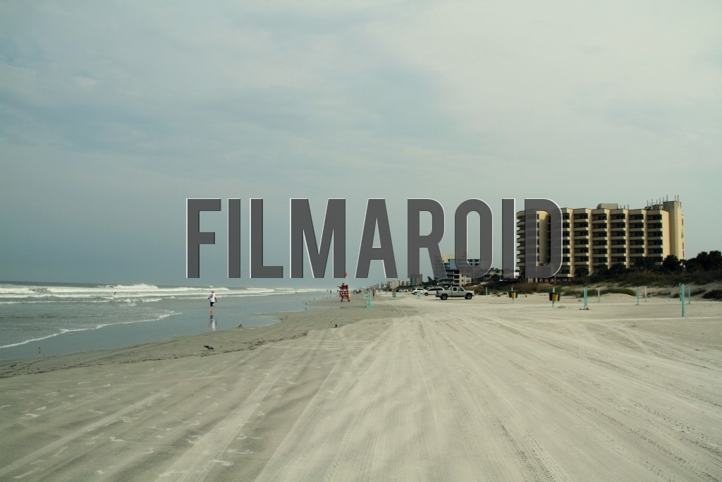 Landscape of a beach in Florida with waves buildings and people seen far in the distance