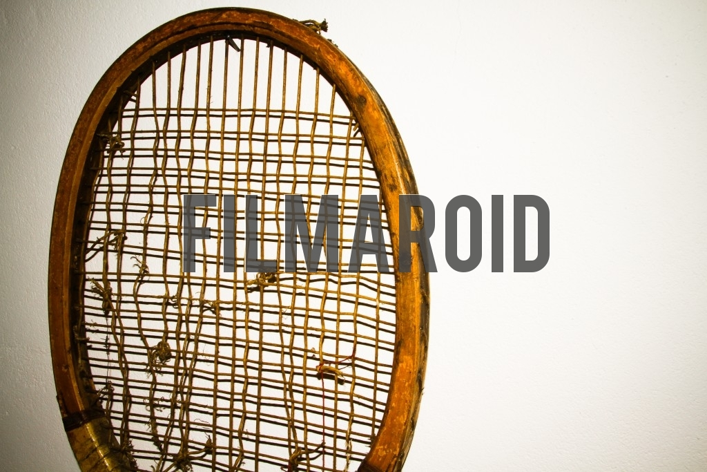 Detail view of an old wooden tennis racket frame with broken strings