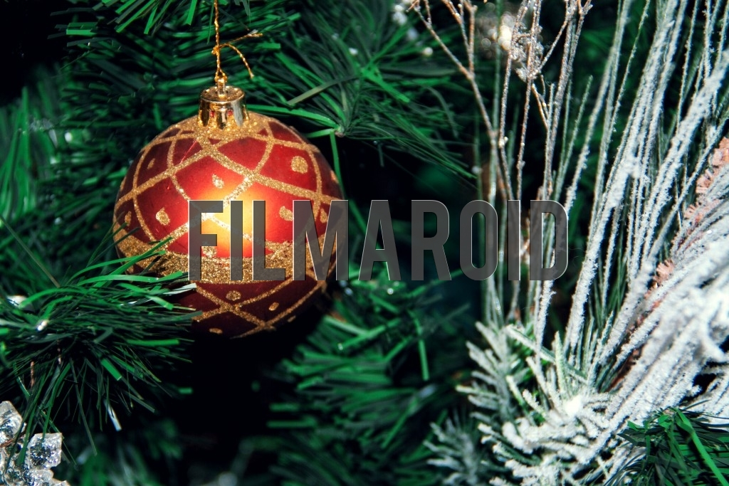 A red Christmas tree ornament decorated with golden glitter