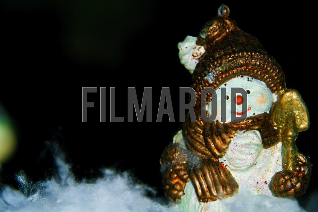 An ornate resin figure of a happy snowman set against a dark night background