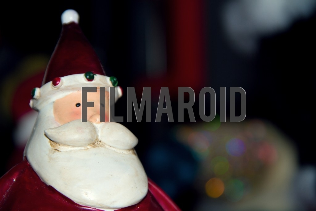A closeup of a resin Santa Claus figure and colorful bokeh background