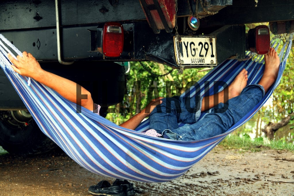 A man comfortably sleeping in a hammock under a truck
