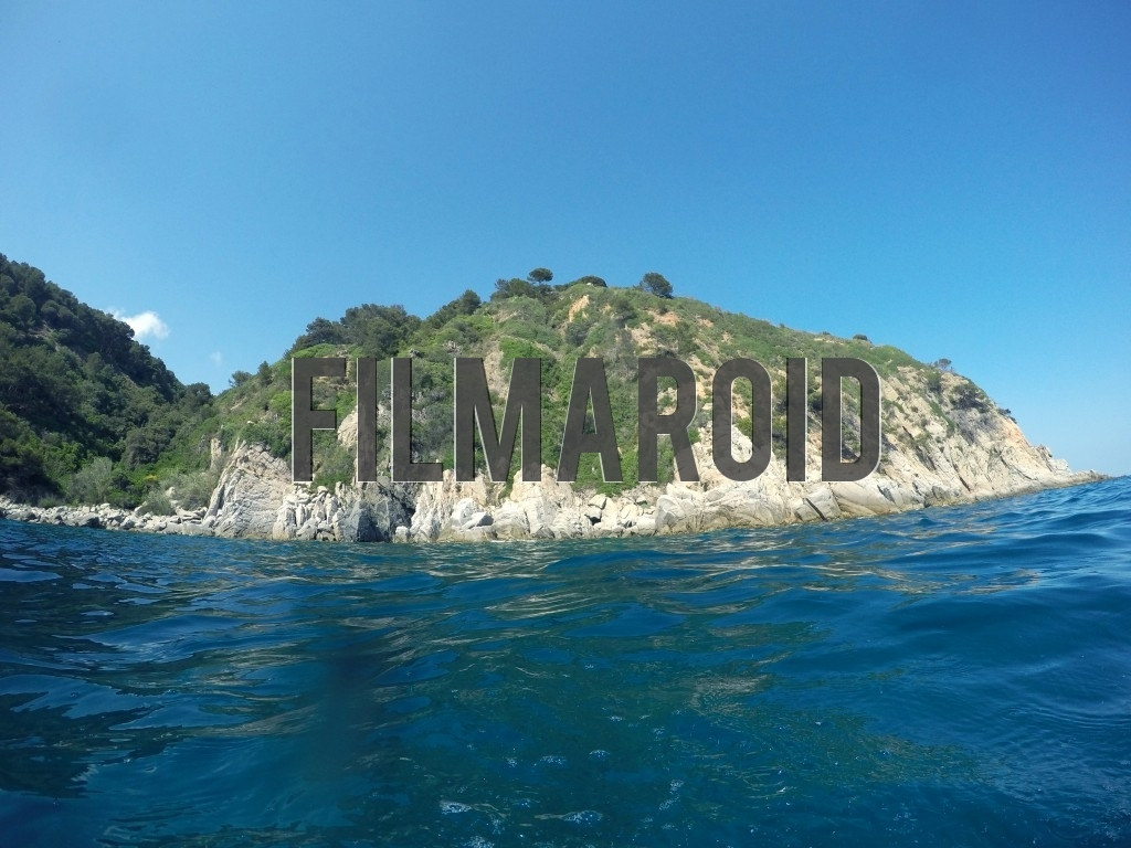 A rocky island seen from the water while taking a swim during a bright summer day