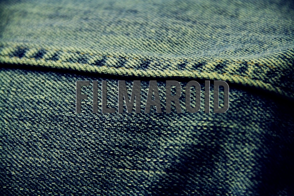 Closeup of an old blue denim fabric with sewing yellow stitches
