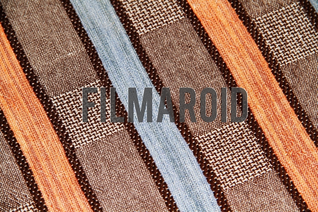 A striped fabric with yellow orange blue and brown tones and squared pattern texture