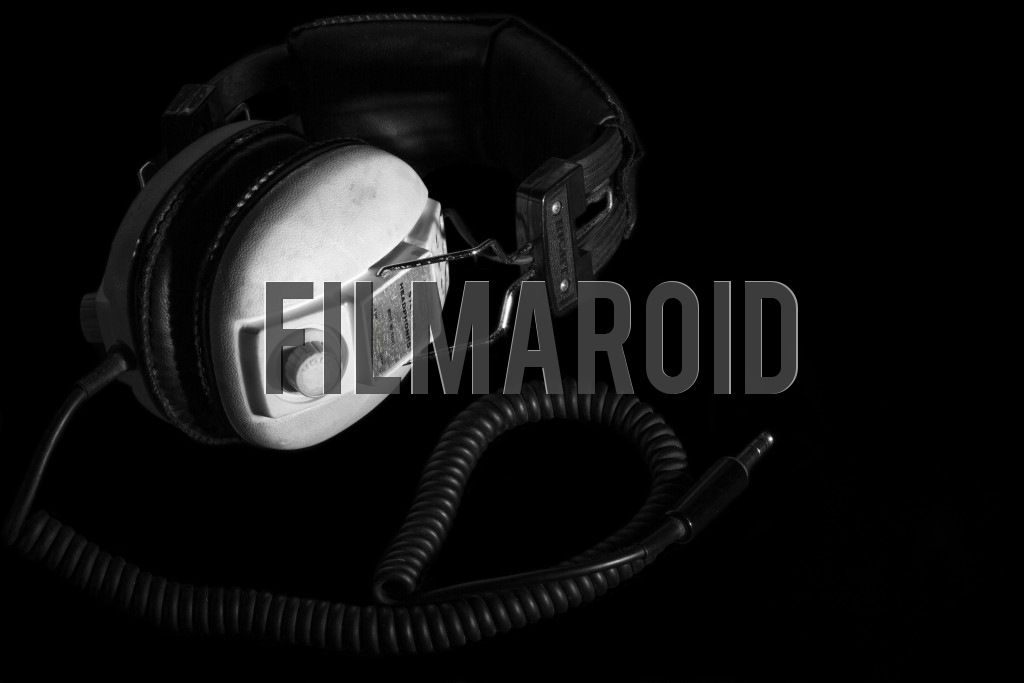 Beautiful vintage headphones with curled thick cable and against a pitch black background