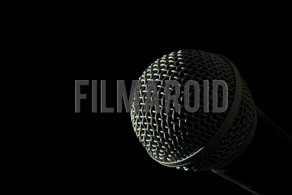 Detail view of the head of a voice microphone isolated against a pitch black background