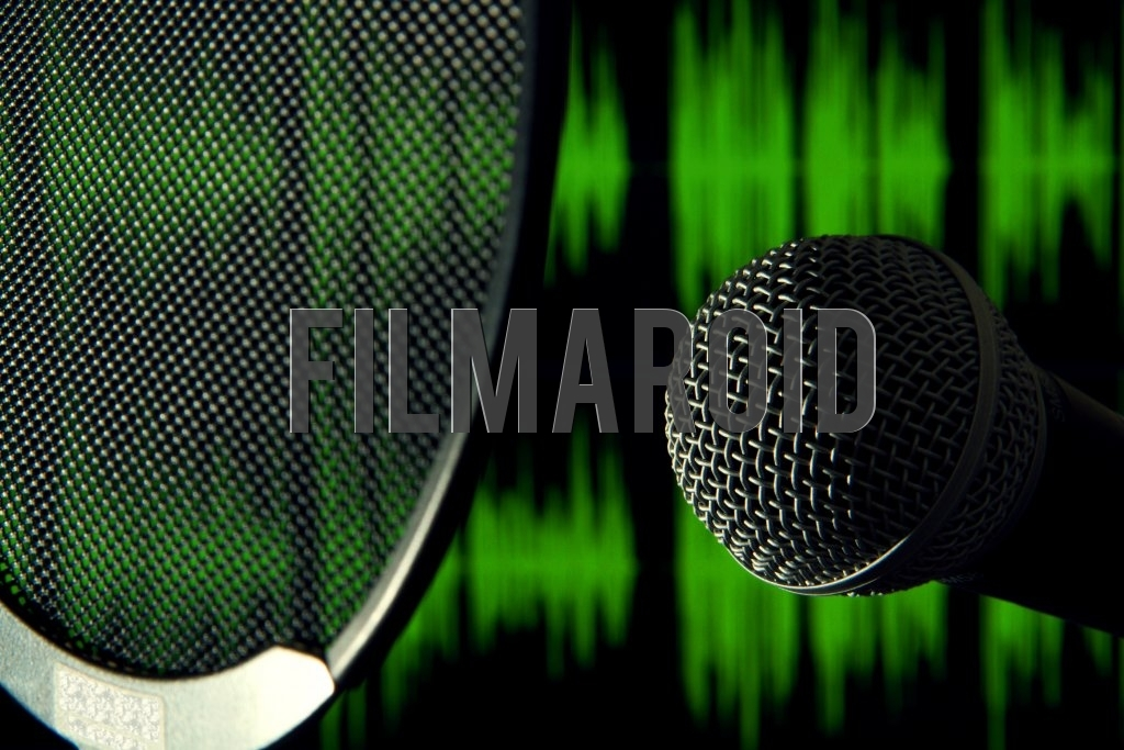 Detail view of a head of a voice microphone with a pop filter in front and green sound waves on the background