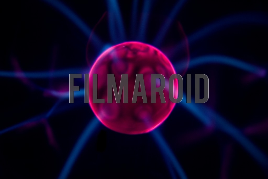 Detail view of bright red Plasma ball center with electric blue rays emitting from it and against pitch black background