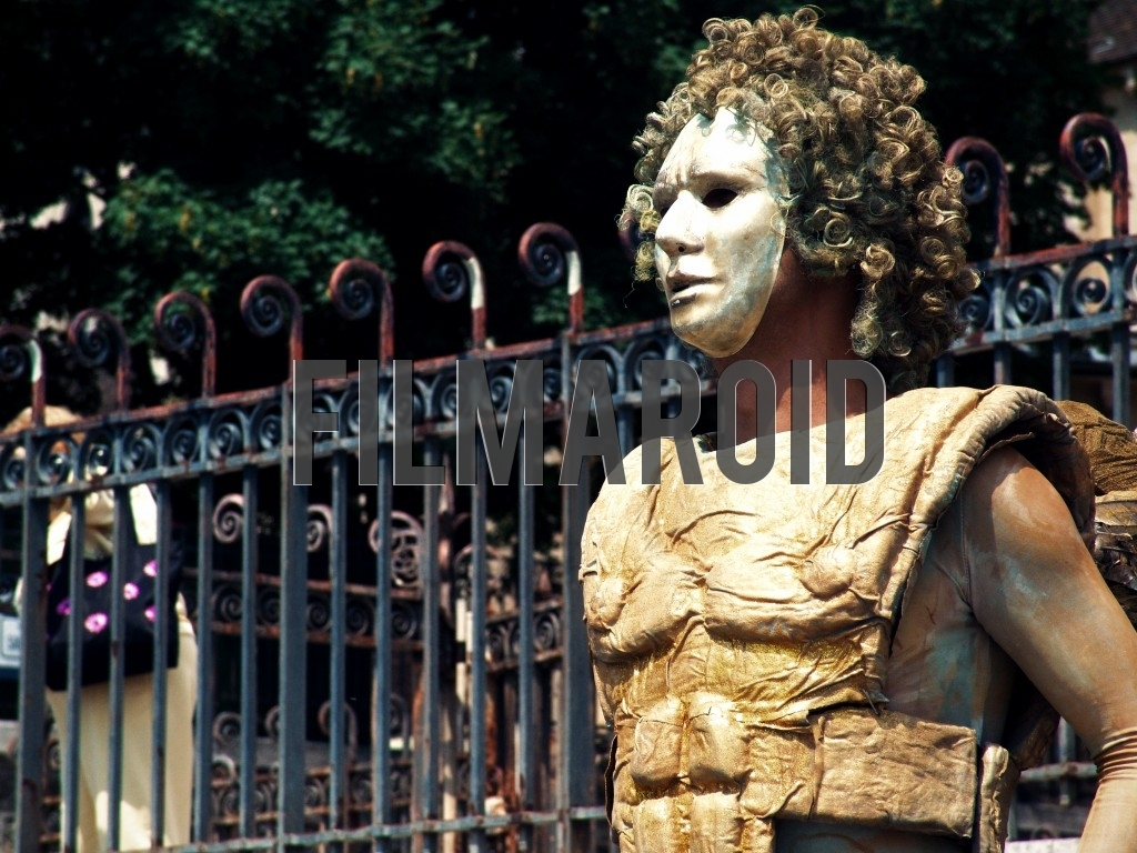 A street artist from the city of Paris France wearing an elaborate golden costume and a wig and white mask
