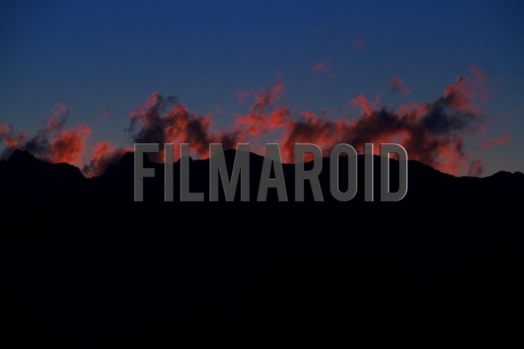 Beautiful afternoon view of the Andean mountain range silhouette with red fire like clouds against blue sky background