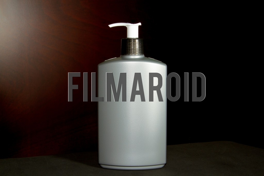 Isolated large gray plastic bottle ideal for body lotion or hands gel against a wooden background