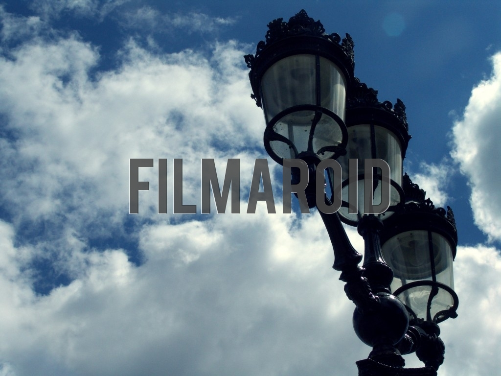 A set of beautiful Parisian lamps against a dramatic cloudy and sunny sky as background