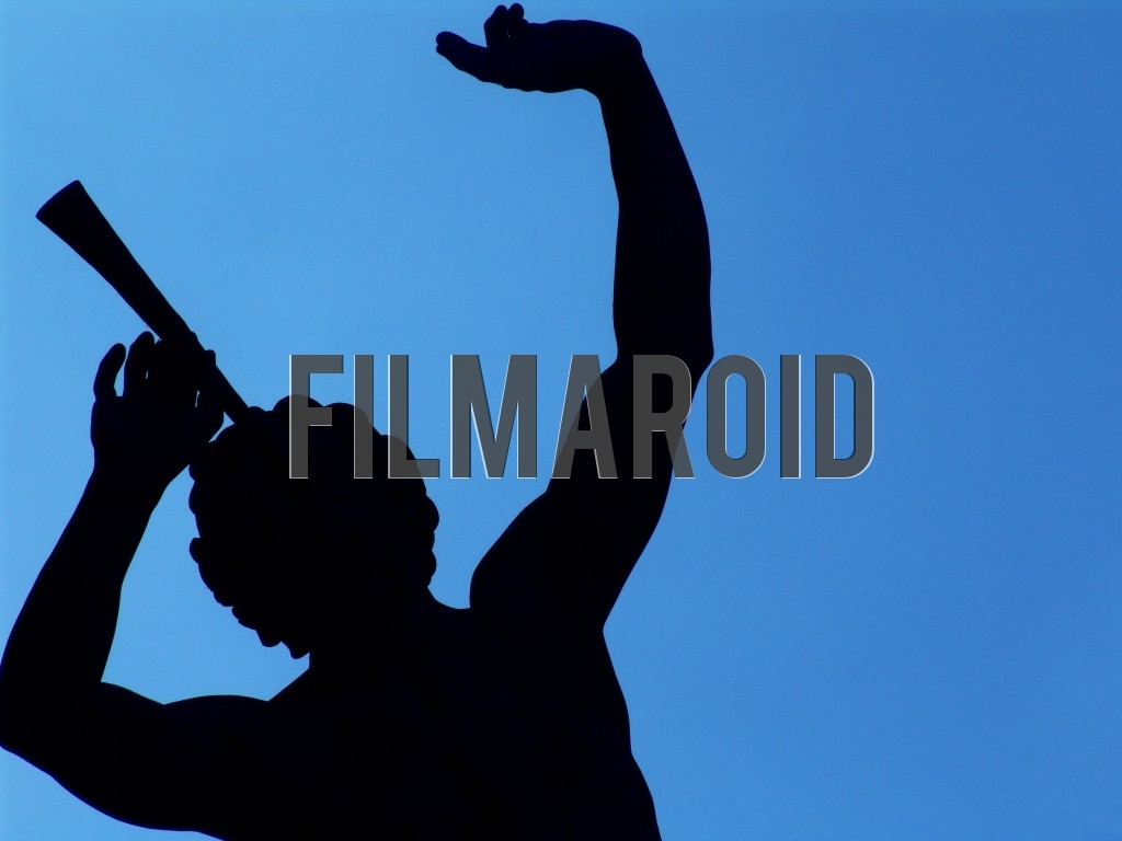 The silhouette of a Parisian statue against an intense blue background