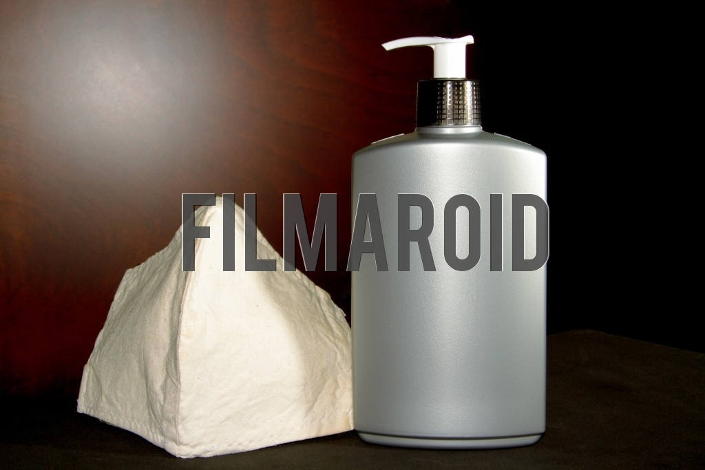 Isolated set of a face mask and a large plastic bottle with hands gel ideal for protecting against coronavirus and the covid19 pandemic
