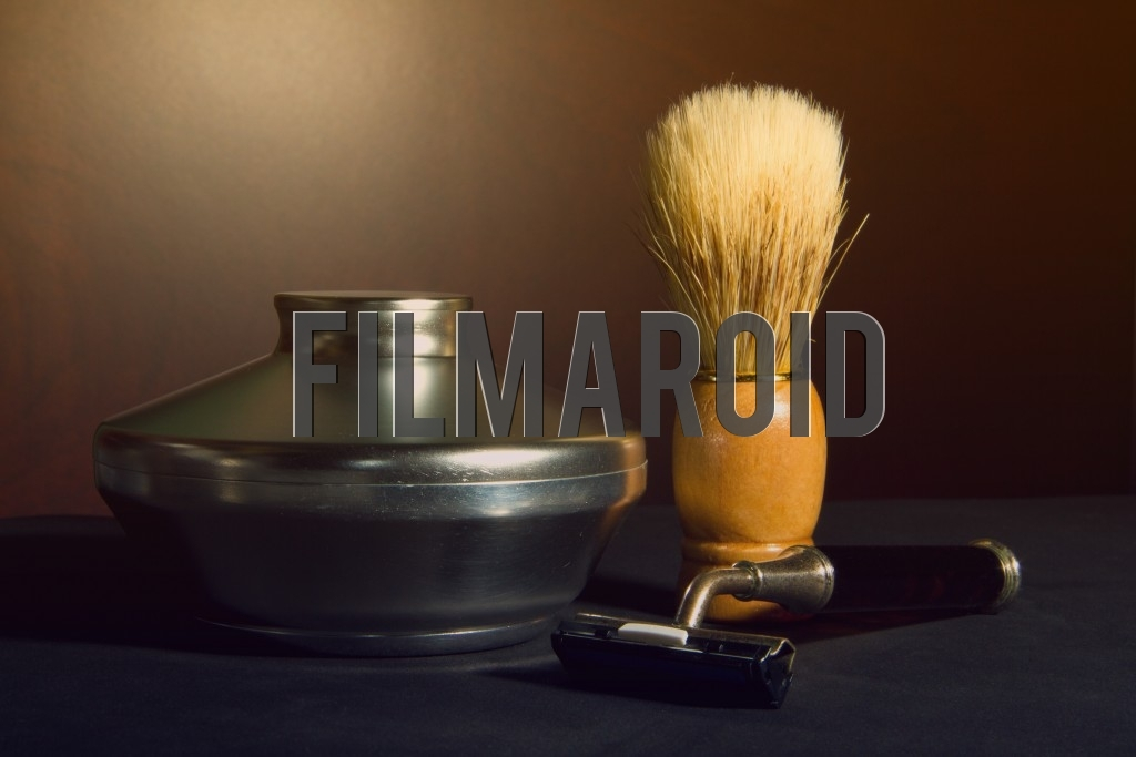 Beautiful vintage shaving kit with razor and camel hair brush against an organic brown wooden background
