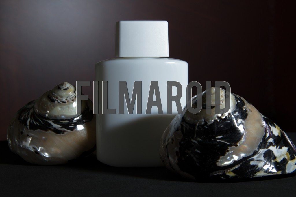 Beautiful and stylish vintage white lotion bottle with a set of colorful shiny seashells against a wooden background